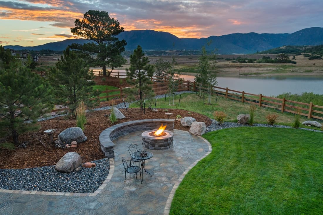 Attractive rural landscaping scene with plantings and fire pit